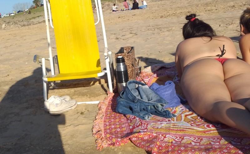 2 gorgeous girls sunbathing on the beach