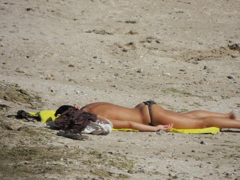 nice topless girl sunbathing on the beach