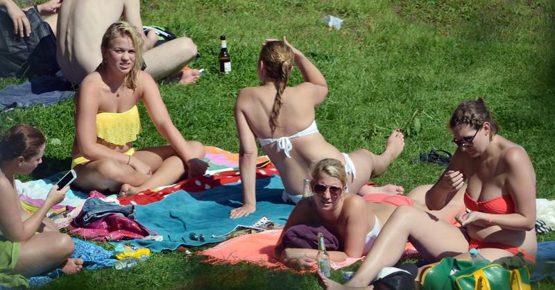 city park sunbathing girls in bikinis